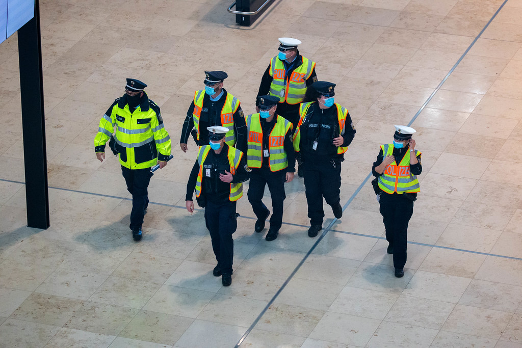 Group of seven police officers wearing face masks and yellow high-visibility vests at new Berlin airport