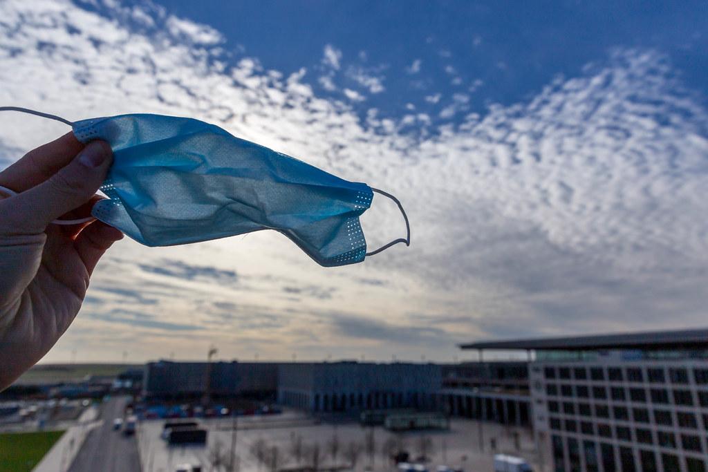 Flughafen BER: Hand hält eine OP Maske mit dem Himmel im Hintergrund und dem ²BAC Gebäude