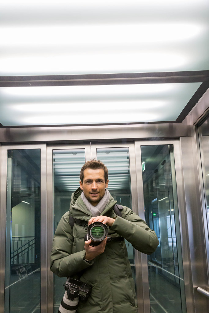 Exploring the new BER airport as a photographer with two professional cameras: self-portrait in the lift