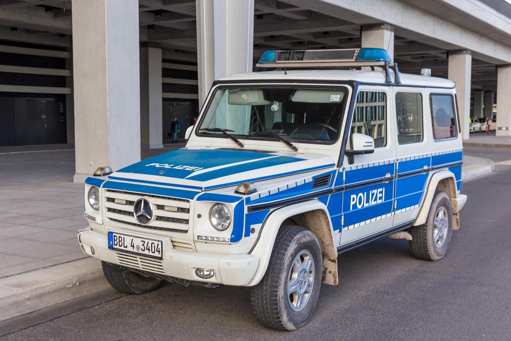 Ein großes Auto der Polizei in Berlin steht vor dem neuen Flughafen geparkt
