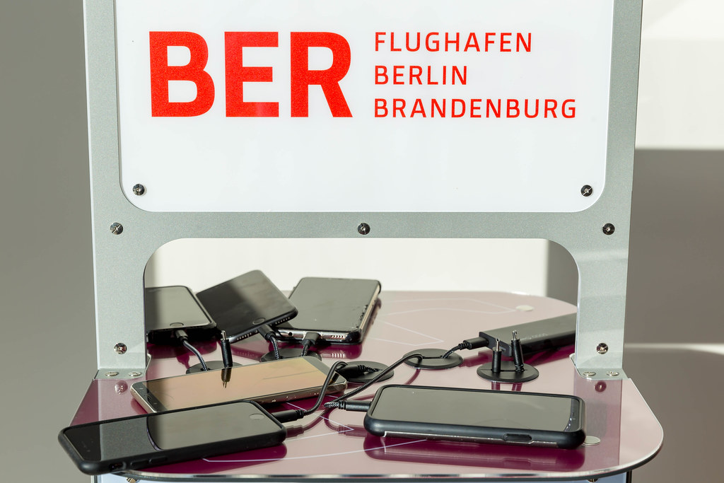 Sechs Handys und eine Powerbank werden an einer Ladestation mit BER-Flughafen-Logo aufgeladen