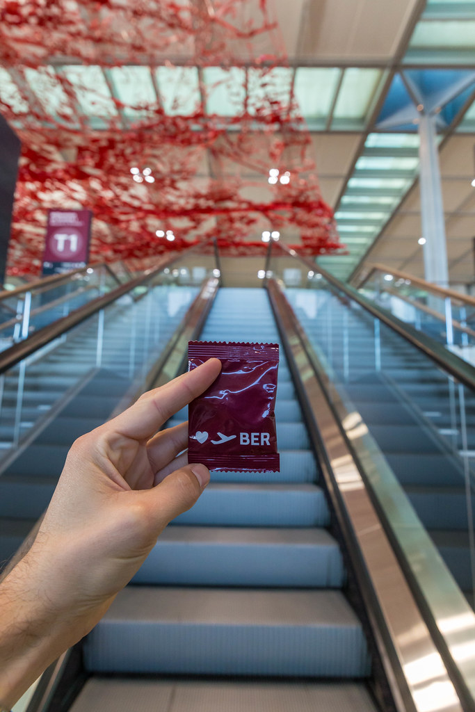 Hand with red gadget of new Berlin airport in front of empty escalators and Pae White's red ceiling artwork