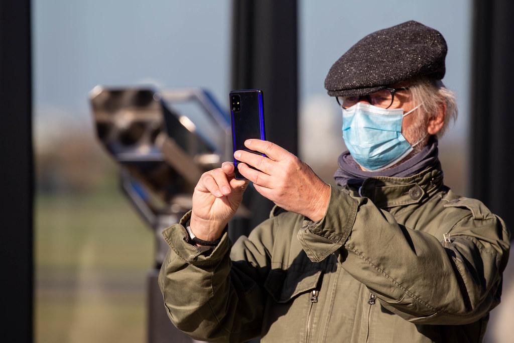 Man with face mask takes a smartphone photo from the visitor terrace of the new Berlin airport BER