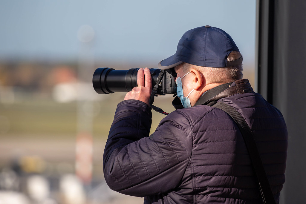 Man with face mask and camera with zoom lens takes photos from the BER airport visitor terrace
