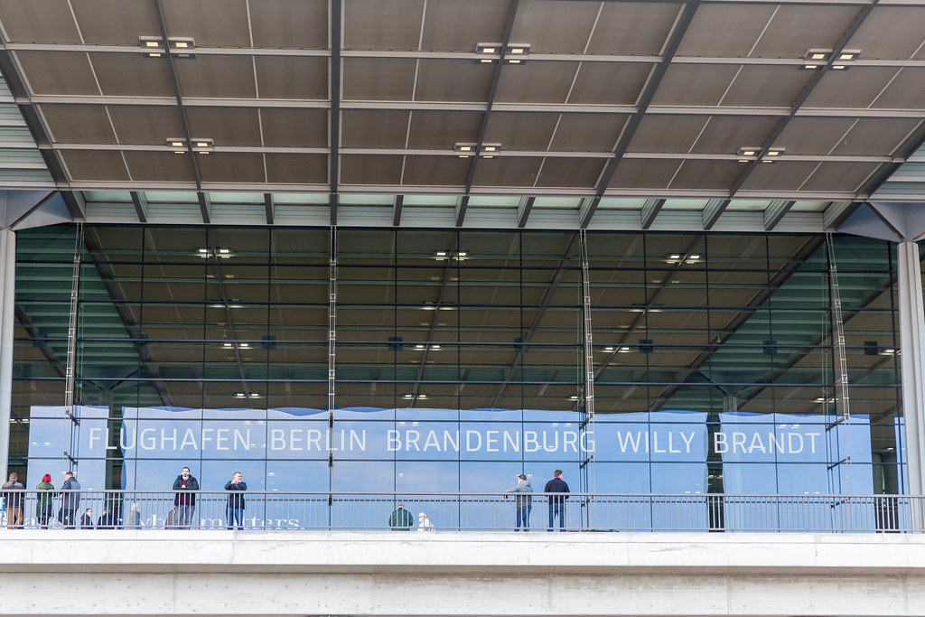 People with face mask and the glass front of Terminal 1 of Berlin Brandenburg Willy Brandt airport