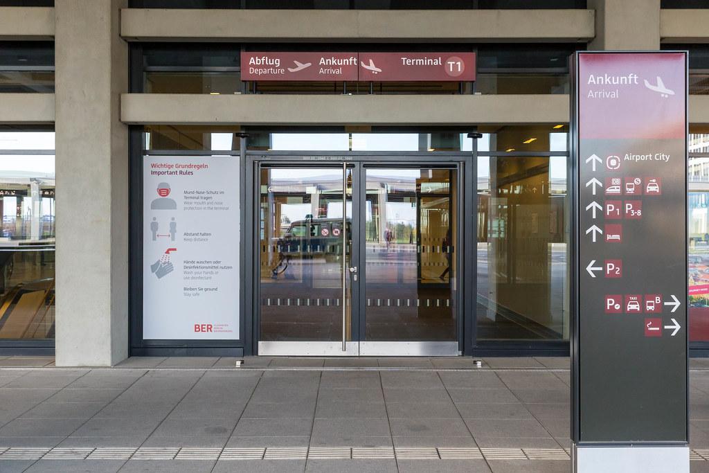Schild mit Corona-Regeln (Maske, Abstand, Hände-Desinfektion) am Eingang vom Flughafen BER T1