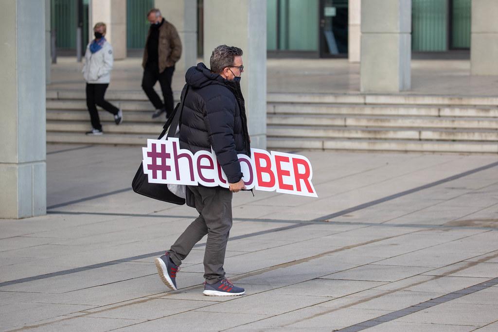 Mann trägt ein Schild mit Schrift #helloBER: Hashtag zur Eröffnung des neuen Flughafens BER in Berlin
