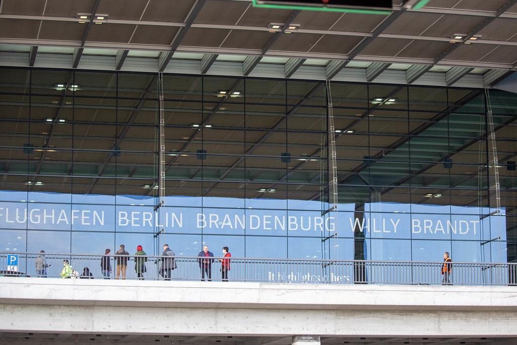 Menschen vor dem BER Terminal 1 mit Schrift auf Glas
