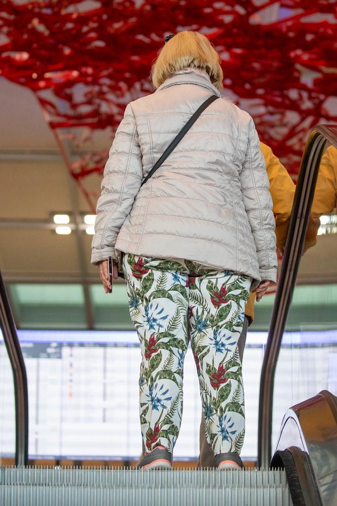 Eine Frau auf der Rolltreppe vom neuen Flughafen BER mit Pae Whites rotem Kunstwerk im Hintergrund