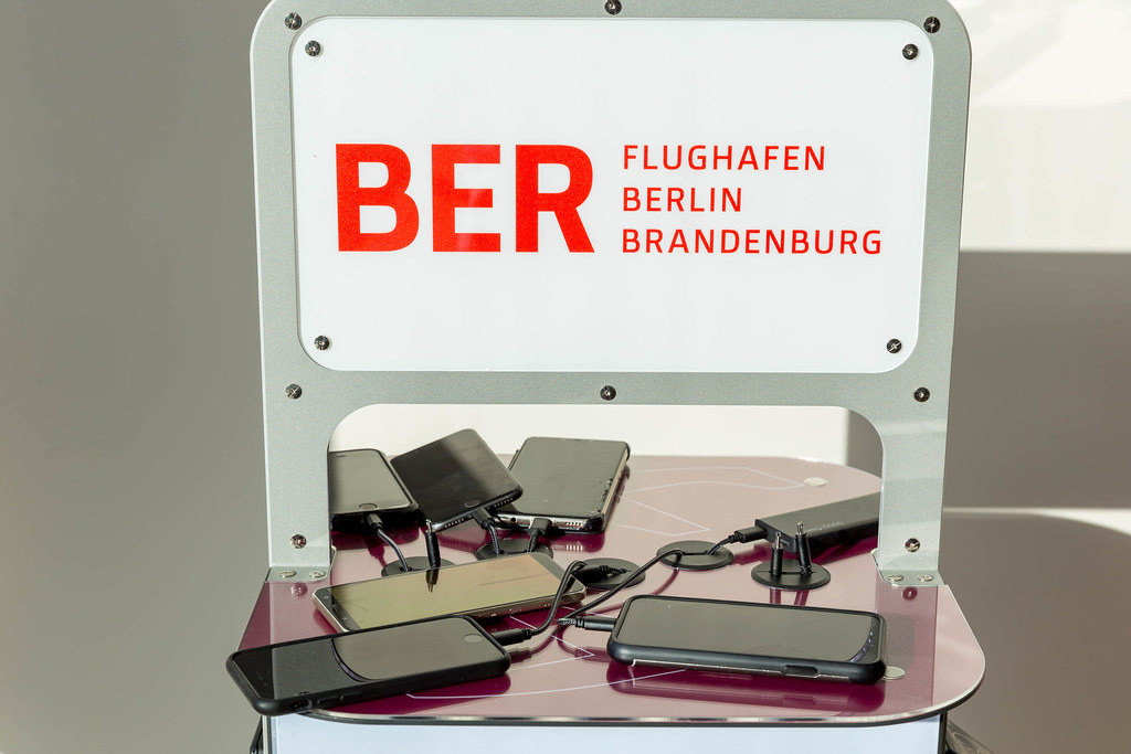 Six mobile phones and a power bank being charged at a charging station with logo of the BER airport