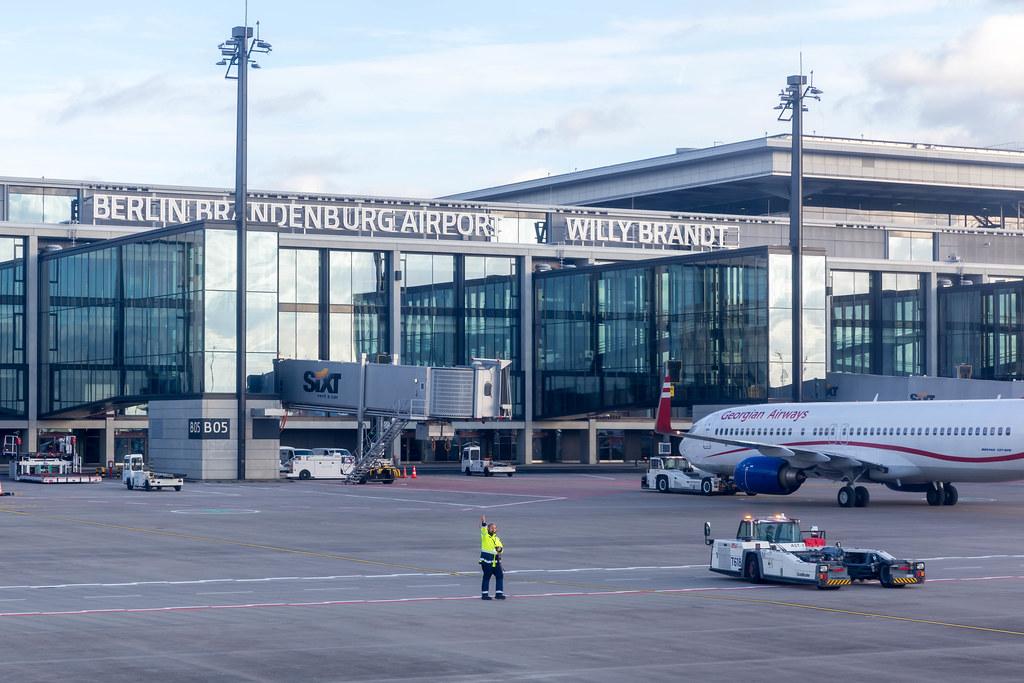 Flughafen BER: Mitarbeiter in Warnschutzjacke und Flugzeug von Georgian Airways auf dem Vorfeld
