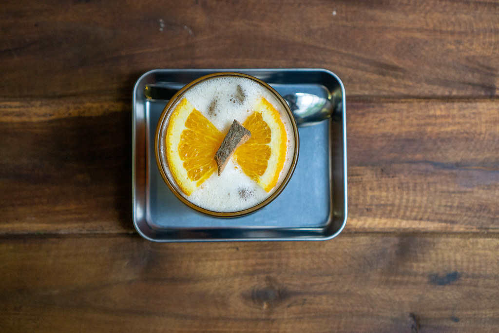 Top View Photo of Cinnamon Orange Iced Tea on a Metal Serving Tray with a Spoon on a Wooden Table