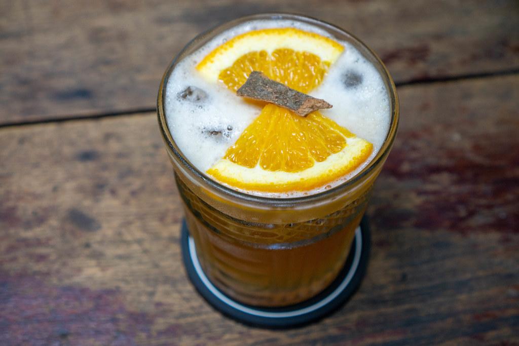 Orangen-Zimt Eistee mit frischen Orangenscheiben und Zimtstange auf einem Holztisch Nahaufnahme