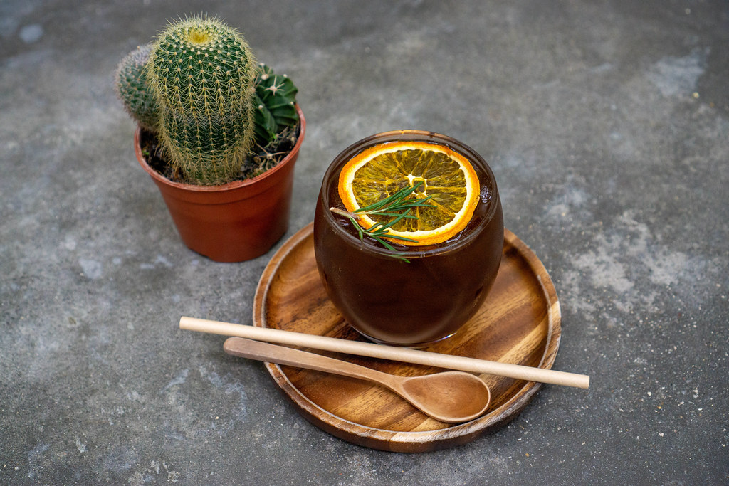 Cold Brew Coffee with Burnt Orange on a Wooden Saucer with Wooden Spoon and Paper Straw next to a Cactus