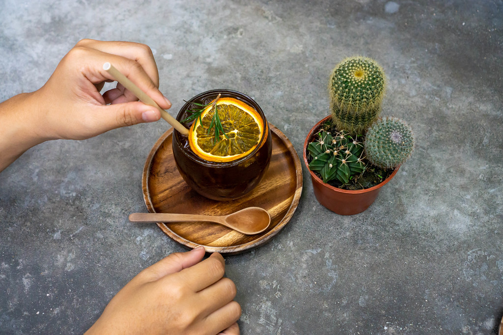 Cactus next to a Glas of Burnt Orange Cold Brew Coffee with a Person touching a Paper Straw