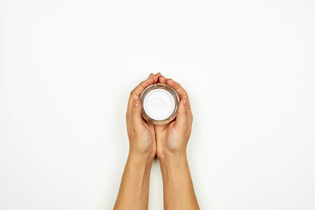 Woman hands holding a cream jar
