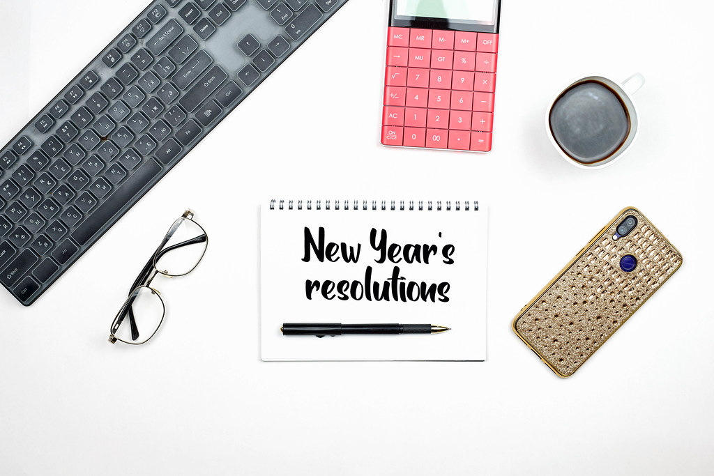 2021 new year resolution text on notepad with office accessories