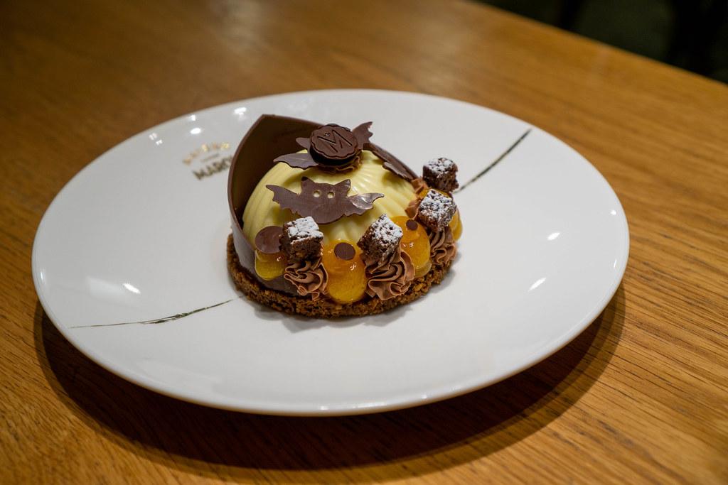 Käsekuchen mit Lebkuchen Boden, Kumquat Creme und Schokoladen Dekoration in Halloween Design