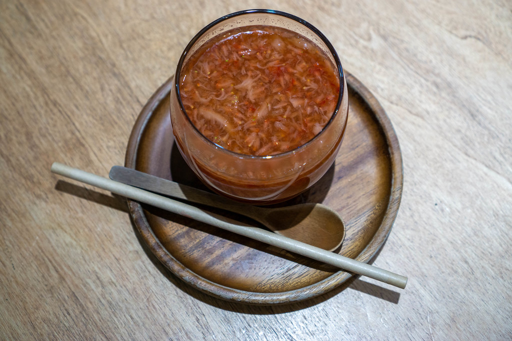 Top View Photo of Hot Strawberry Tea with Paper Straw and Wooden Spoon on a Wooden Saucer