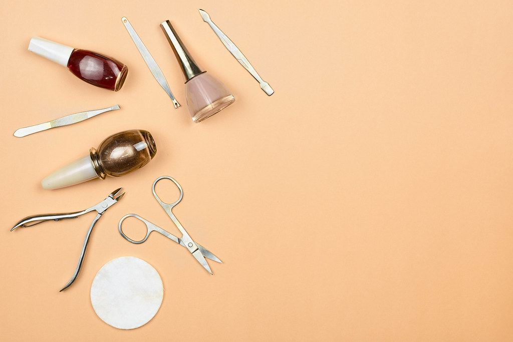 Set of manicure and pedicure tools on trendy pastel background. Professional instruments for nail care