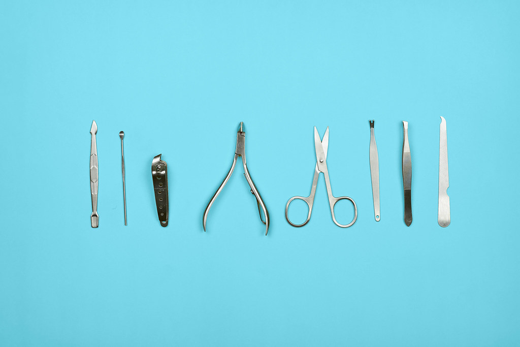 Manicure tools on bright blue background