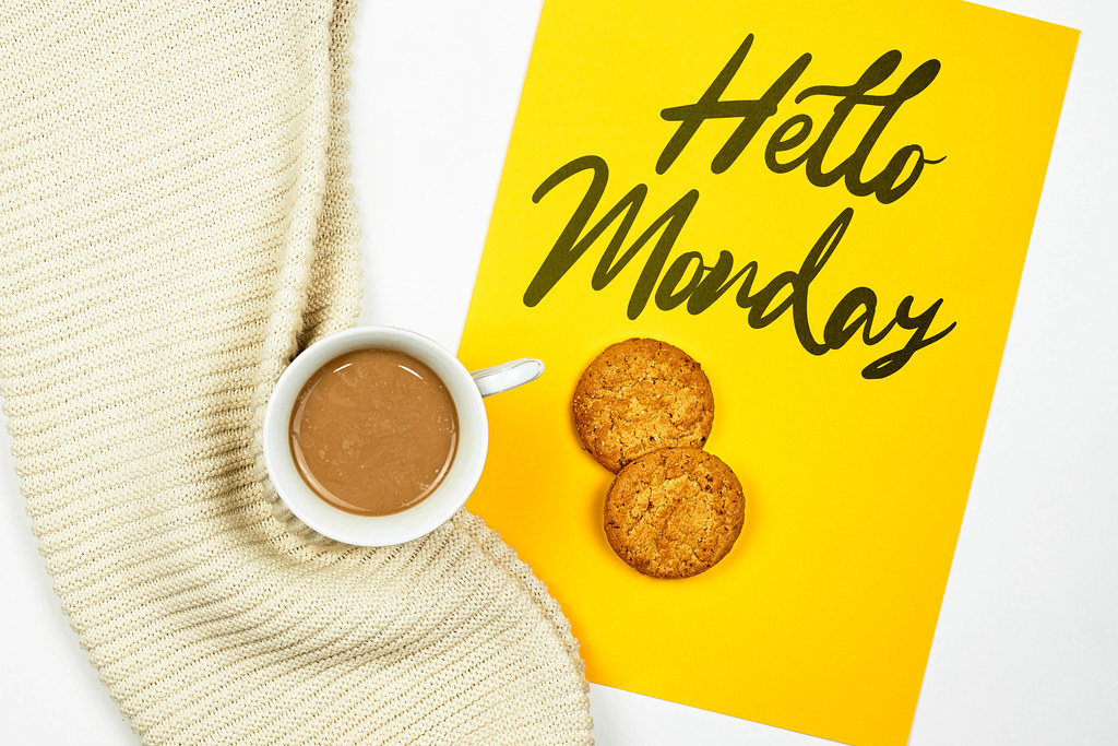 Bright yellow notepad with Hello Monday text on it and cup of coffee with a warm scarf