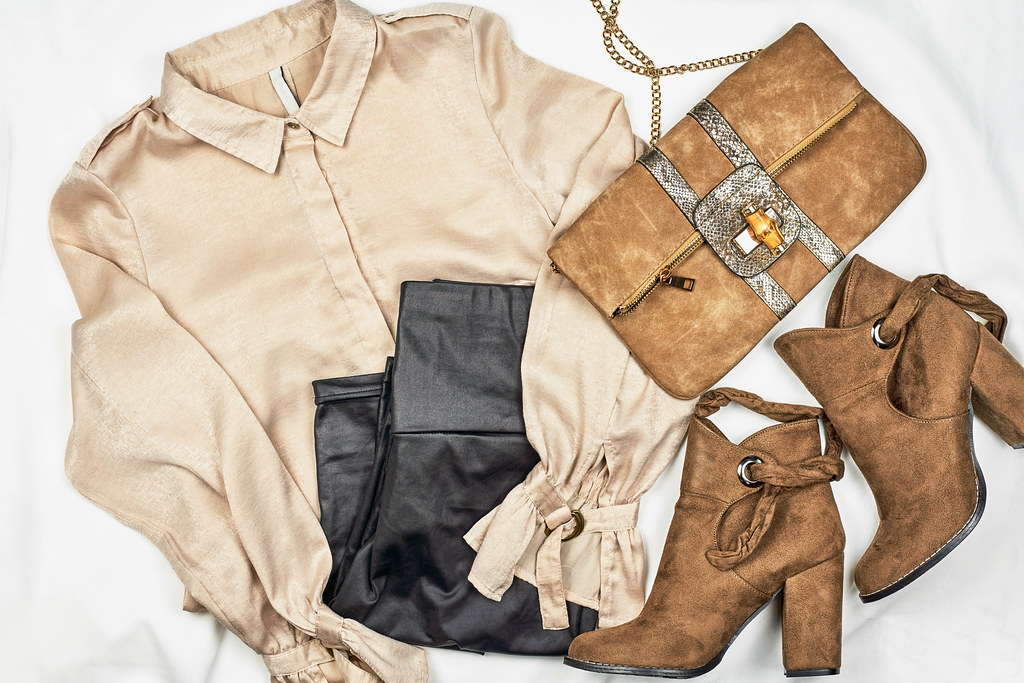 Women's clothing set - skirt, boots, shirt, leather bag on light background