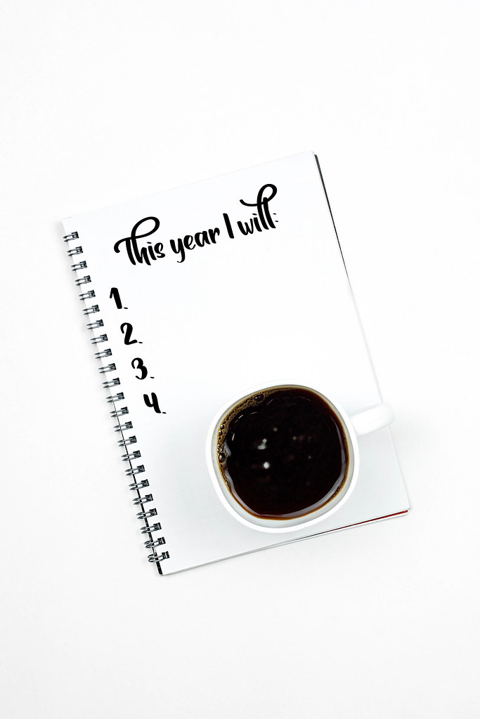 New year resolutions on notebook with a cup of black coffee on white background