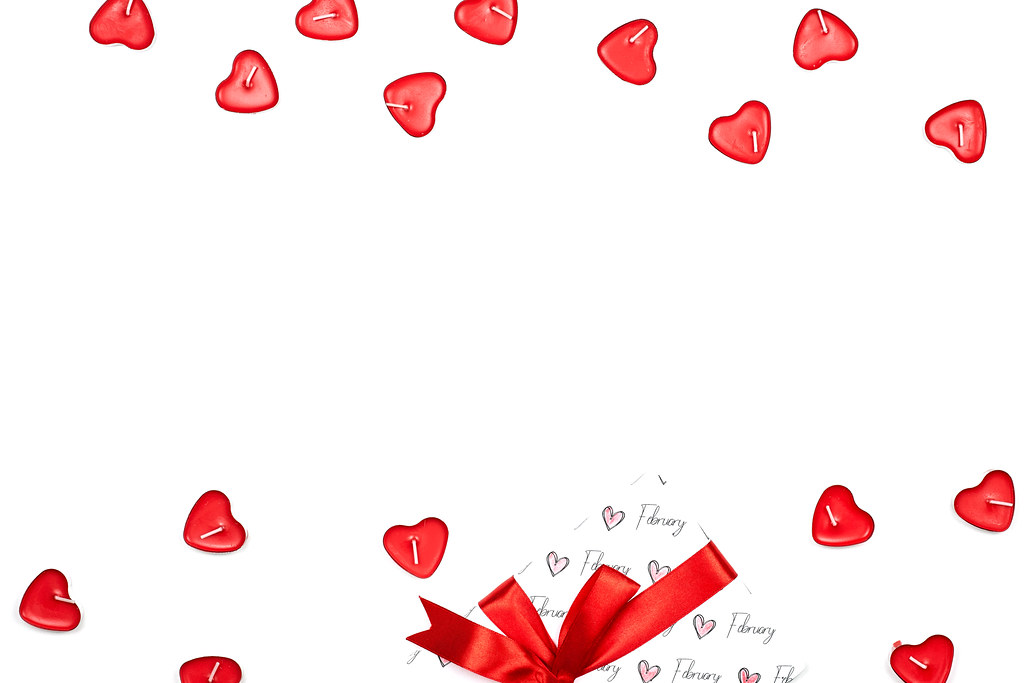 Bright Valentine's day background with heart-shaped candles and giftbox