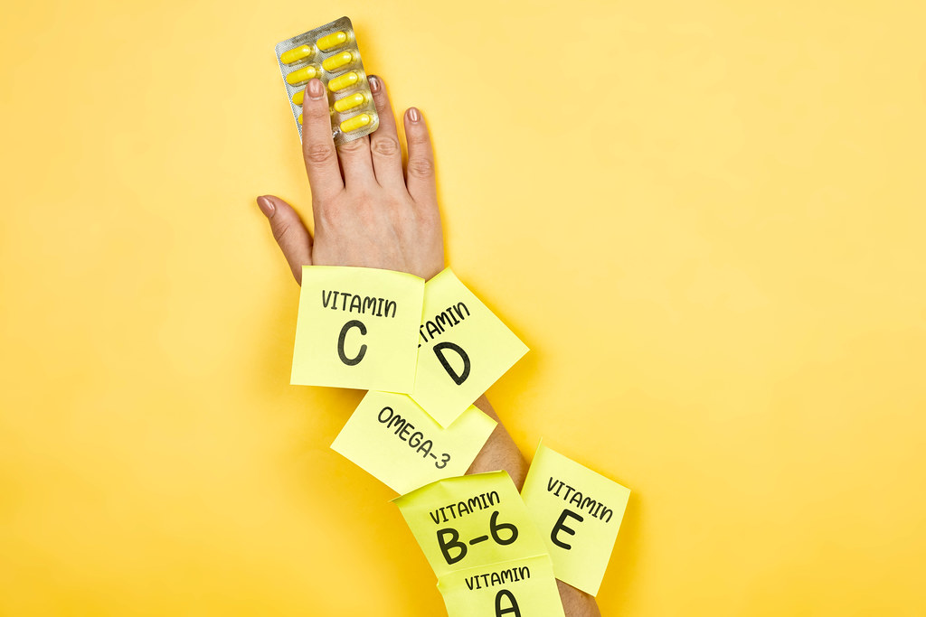 Woman holds vitamin pills on yellow