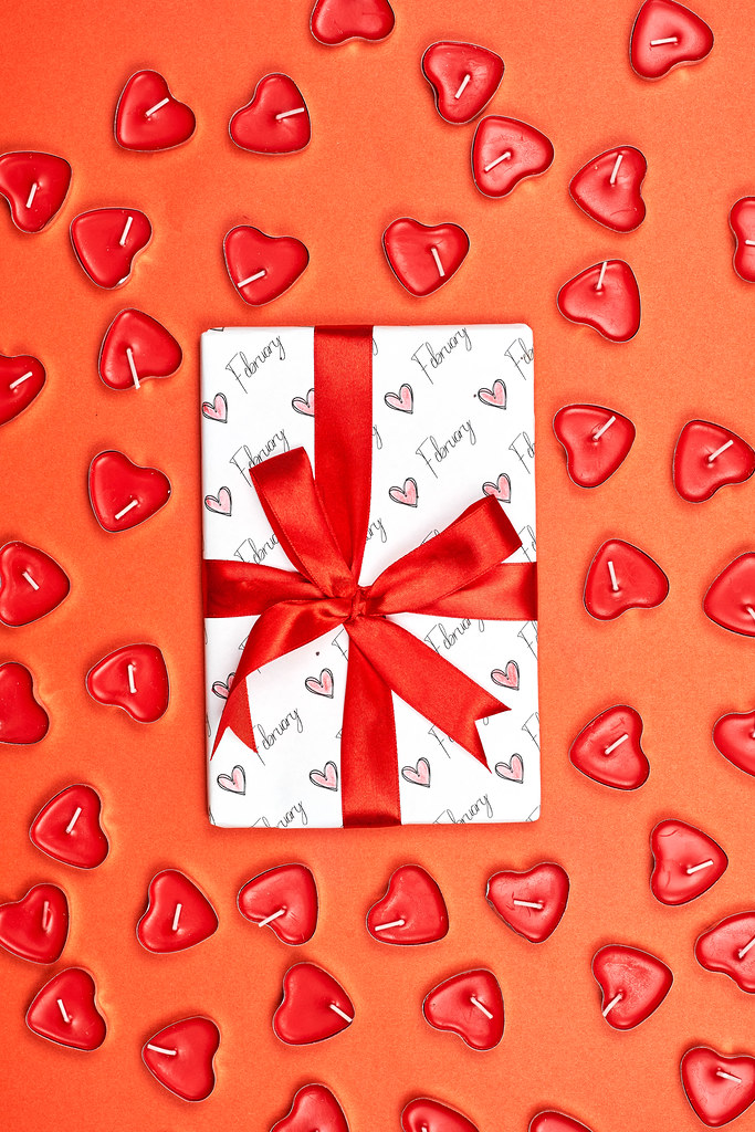 White present box for valentine day and lot of heart-shaped candles around it