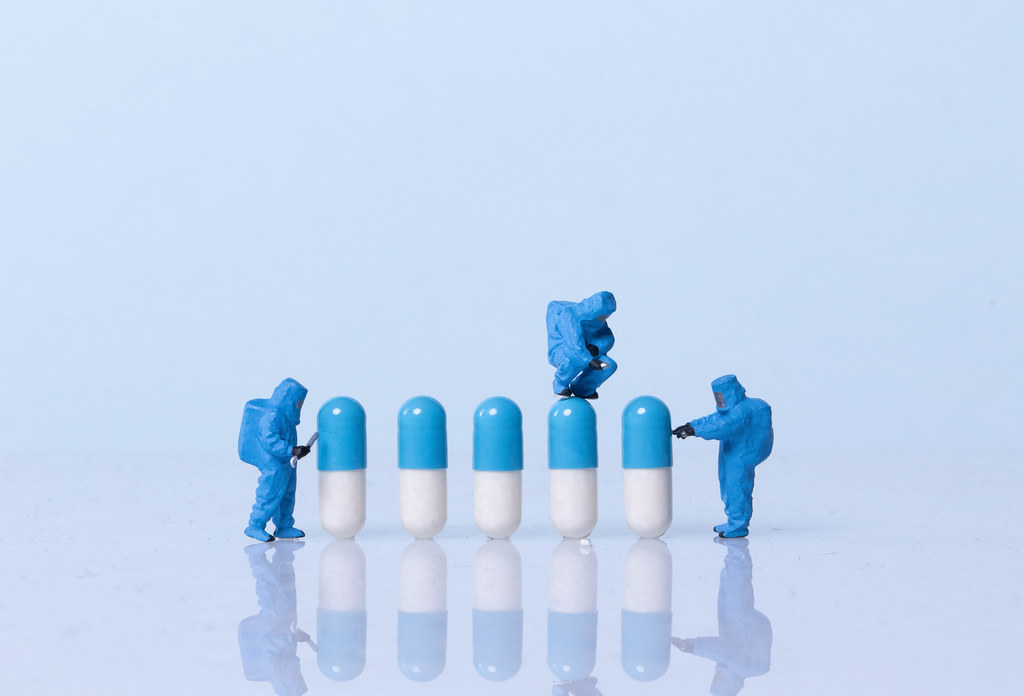 Miniature workers in safety uniforms and pills on light blue background