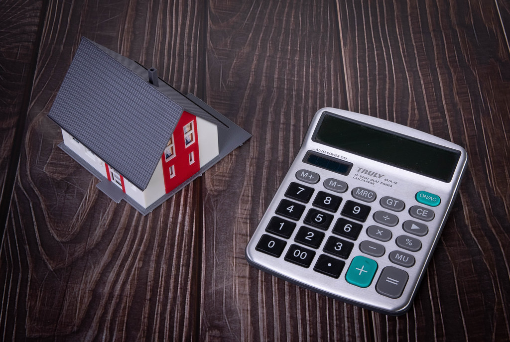 House and calculator on wooden table