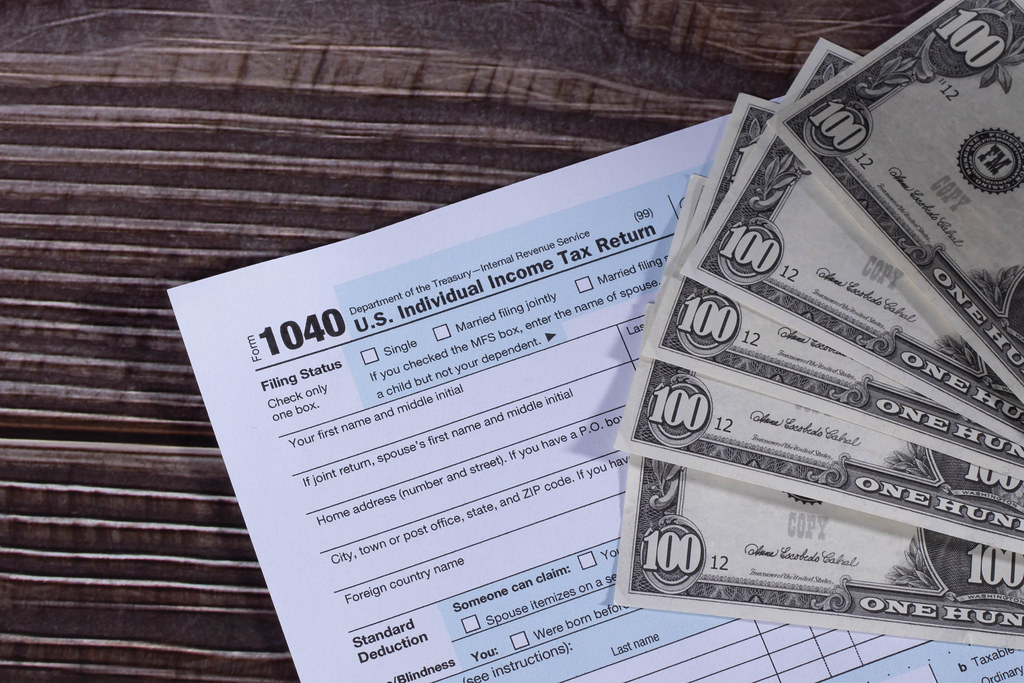 USA Tax Form 1040 with 100 dollars bills