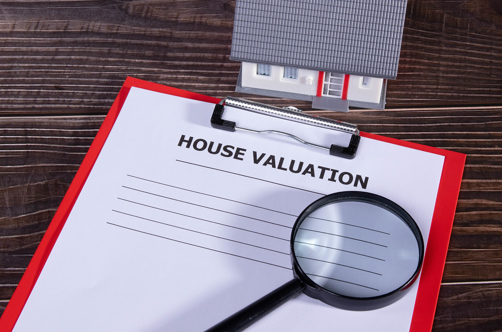 House valuation document with small family house and magnifying glass on wooden table