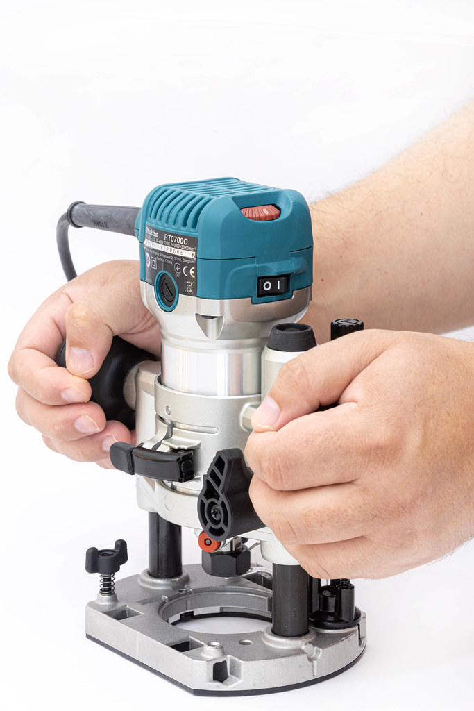Makita Hand Router in the hands of the carpenter