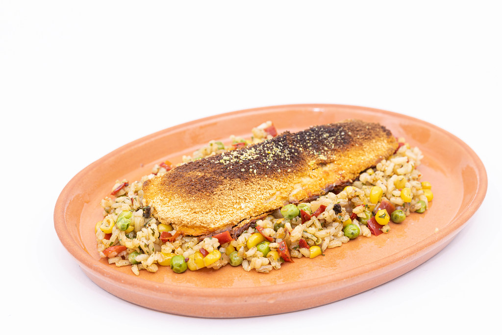 Cooked Rice with Vegetables and fryed Hake served on the plate