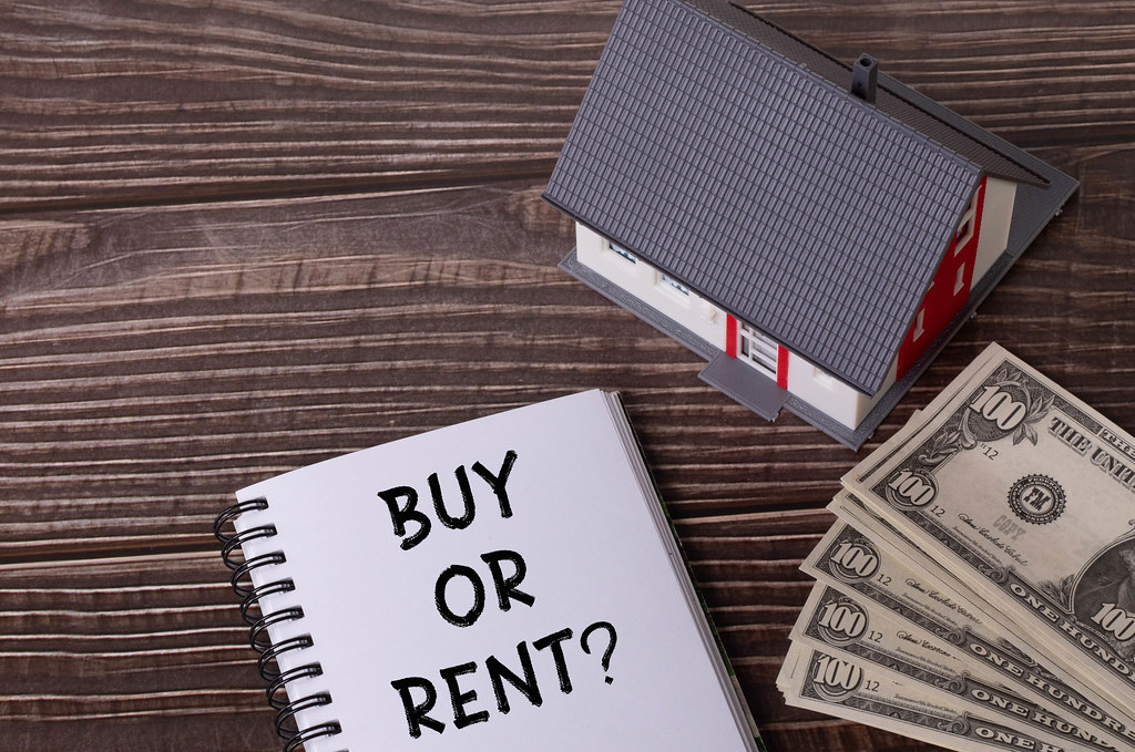 Small house with money and notebook with Buy or Rent text