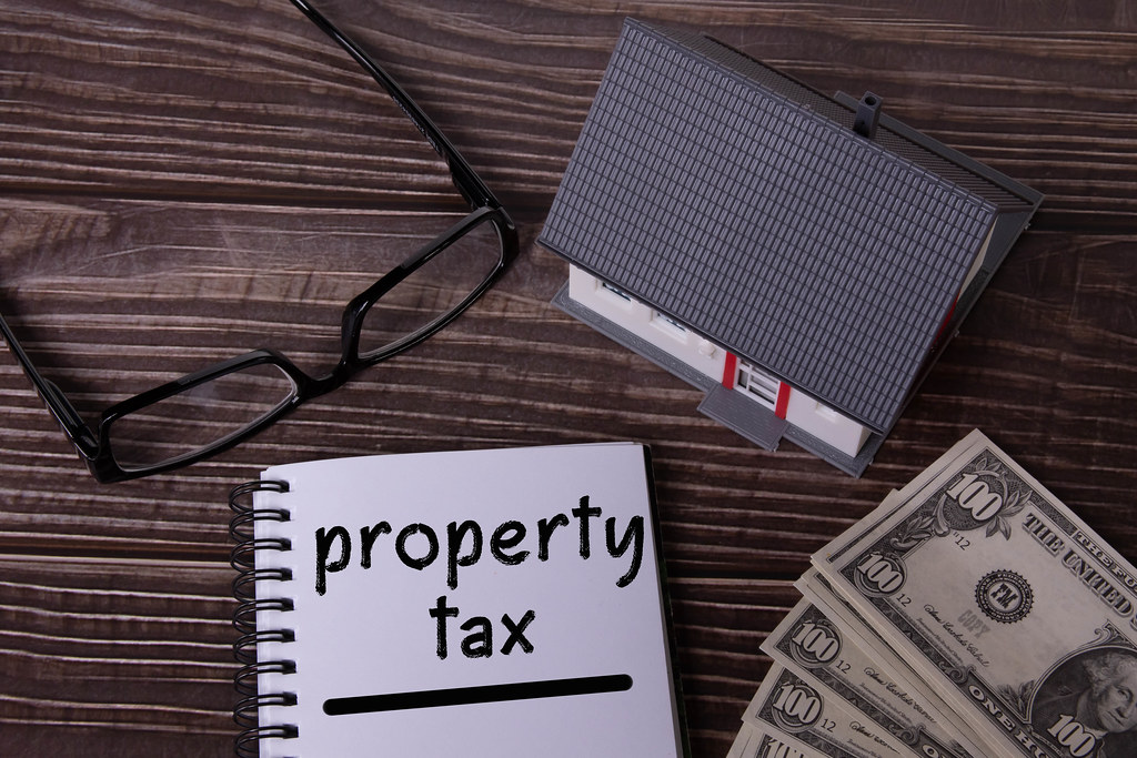 Small house with money and notebook with Property tax text