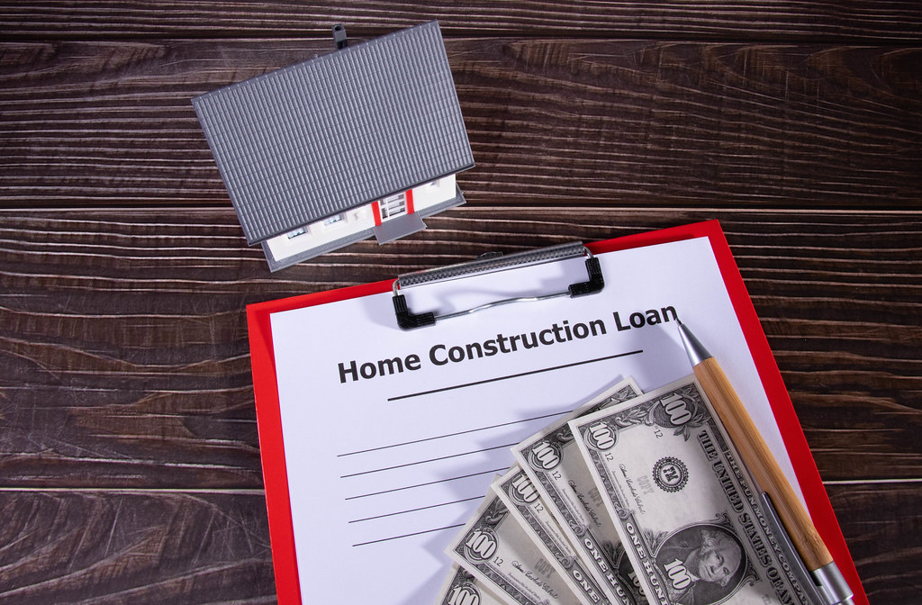 Construction loan form on a wooden table with money and small familiy house