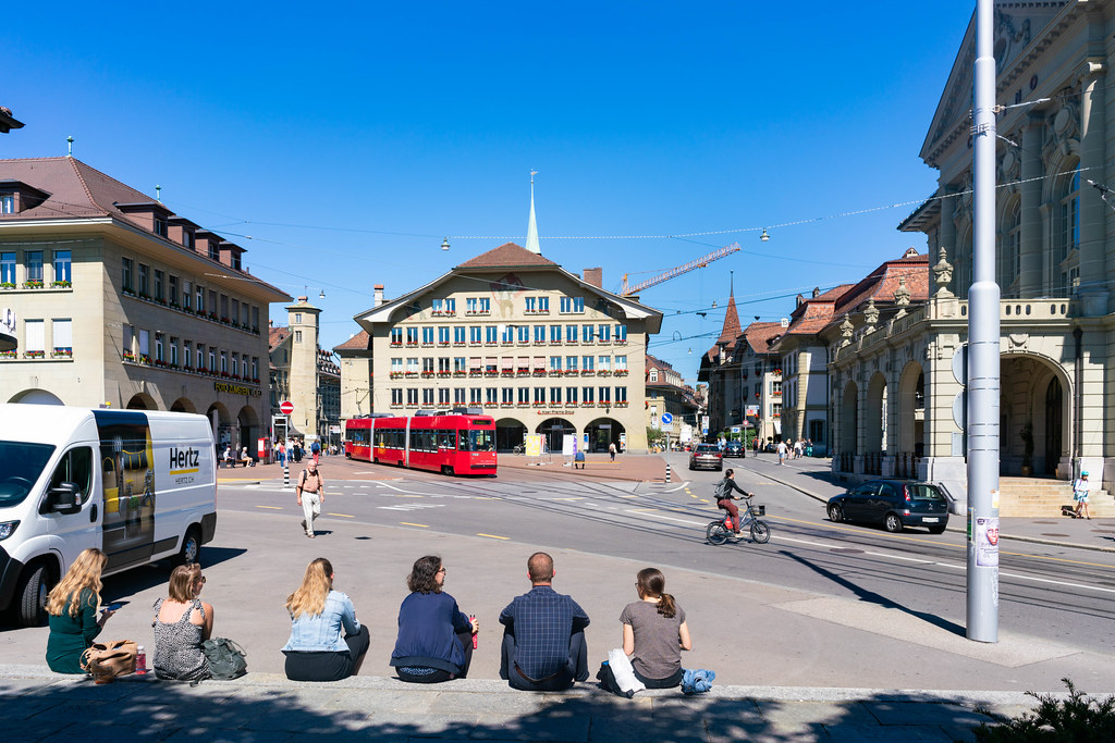 People sitting down on stairs and relaxing in the historical center of Bern, Switzerland