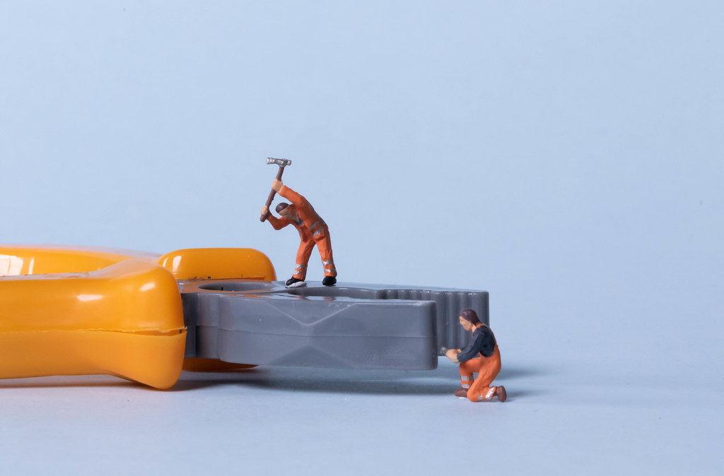 Two miniature workers with pliers