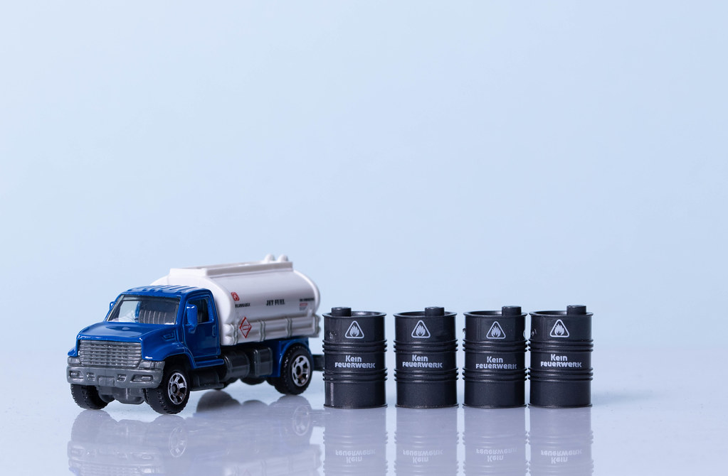 Oil truck and oil barrels on ligh blue background