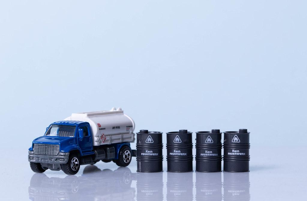 Oil truck and oil barrels on ligh blue background