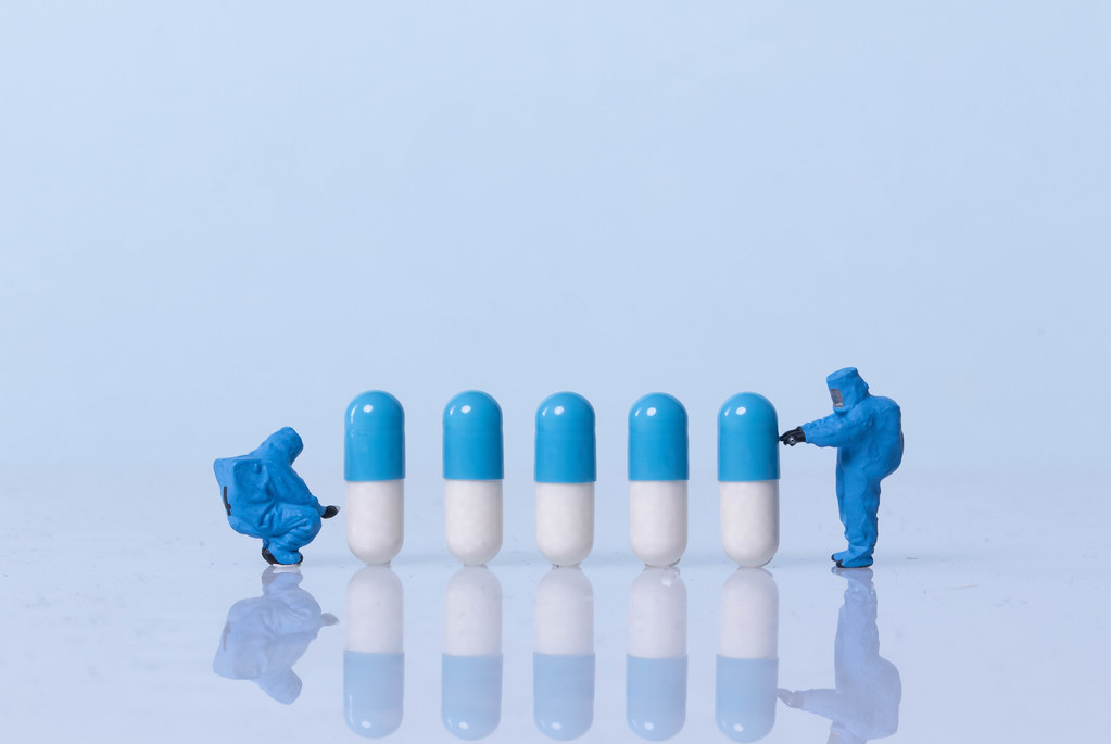 Miniature workers in safety uniforms with pills on light blue background