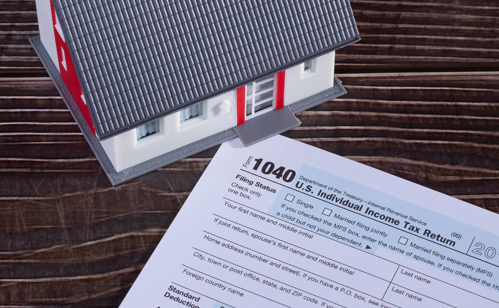 USA tax form 1040 and house on wooden table