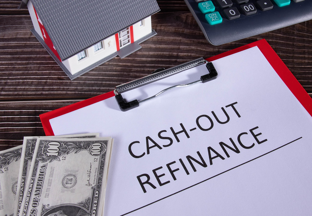 Cash out refinance documents, calculator, money and small family house