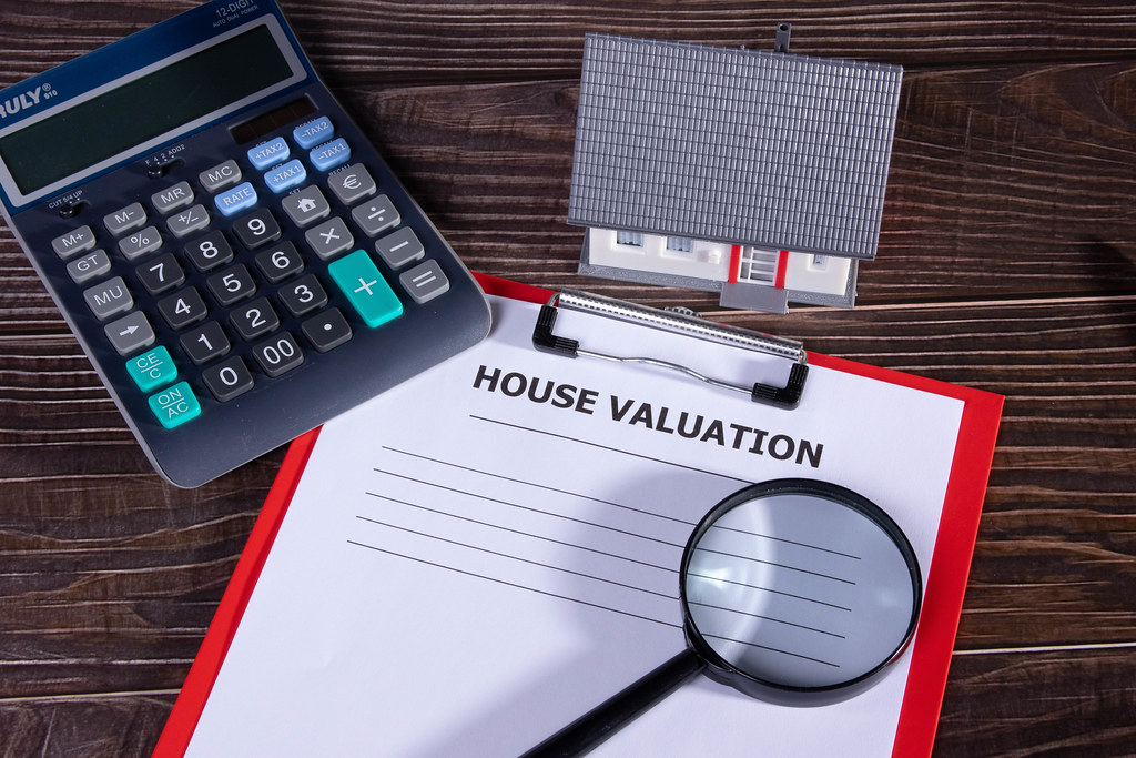 House valuation document with small family house, calculator and magnifying glass on wooden table