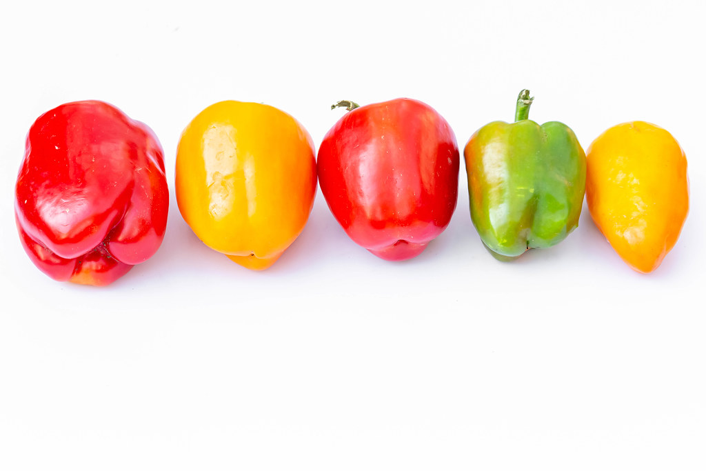 Bell peppers yellow, green and red on white background