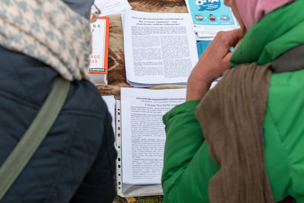 Two participants demo over anti-Covid measures read printed pamphlets on conspiracy theories